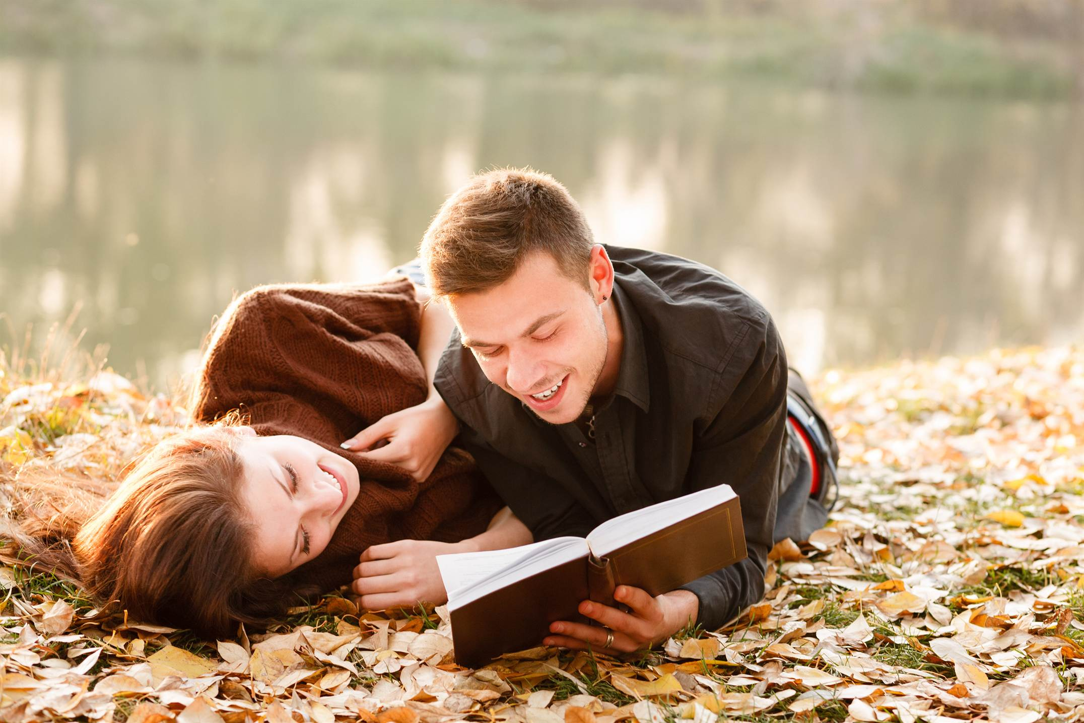 young man lying down near lake reading to his girlfriend book