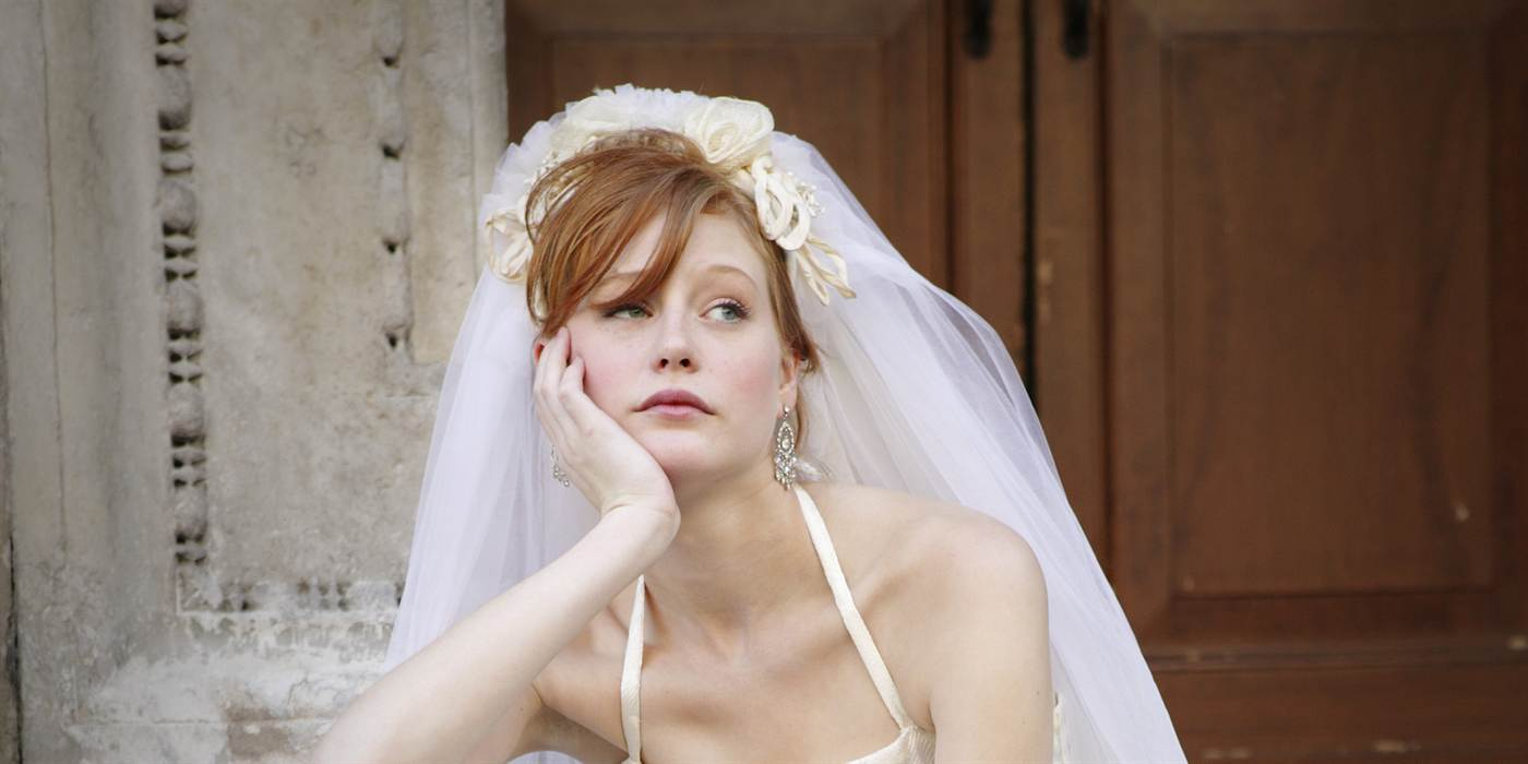 Young bride sitting on steps to doorway, head resting in hand