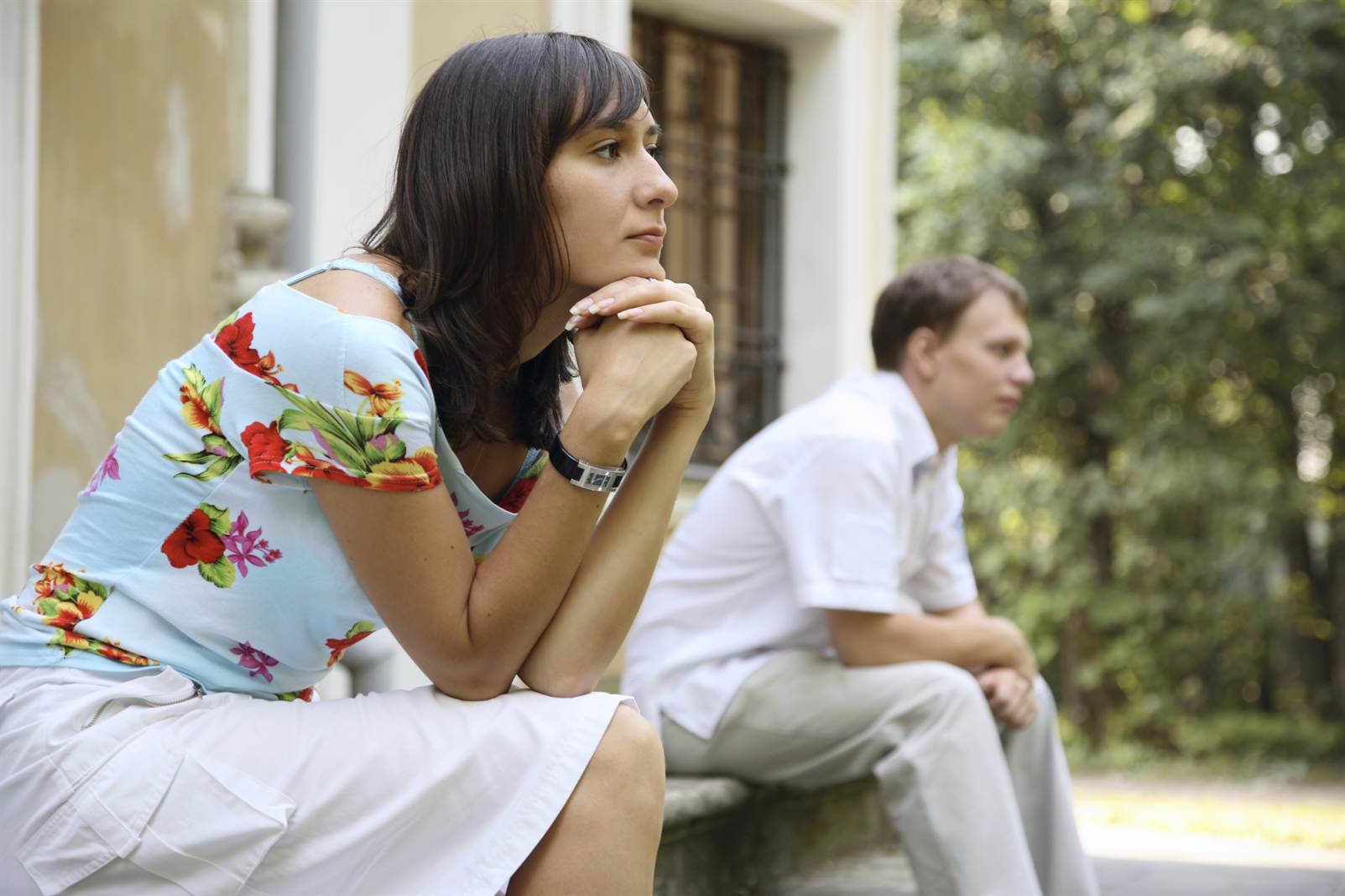 Young sad woman and man sitting on marble steps in park, selective focus