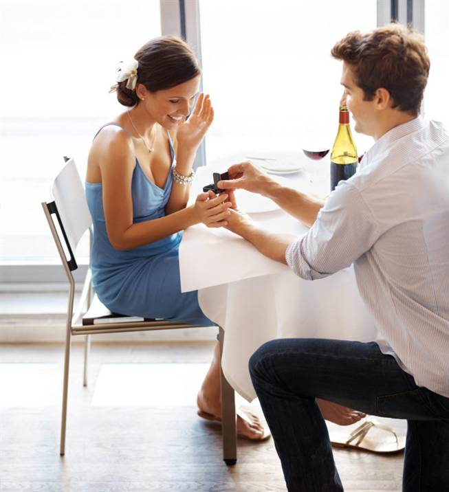 Happy young man making a proposal giving engagement ring to his fiancee in a restaurant